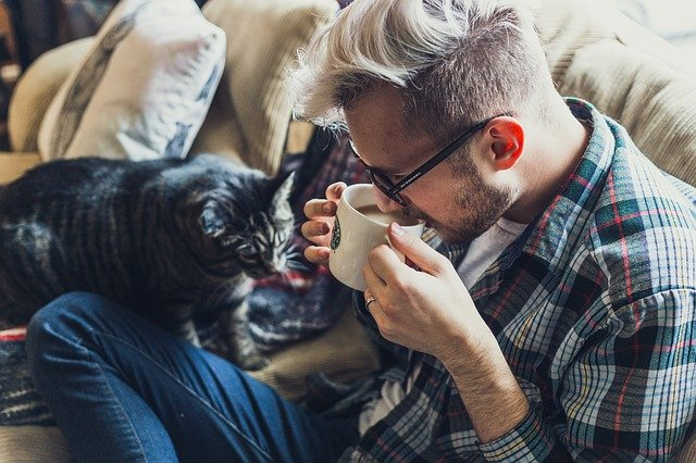 man relaxing at home with his cat and a hot drink