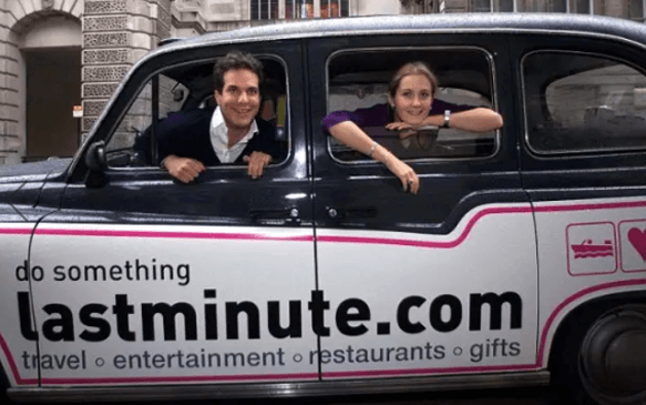Founders of lastminute.com Martha Lane Fox and Brent Hoberman learning out of a branded taxi