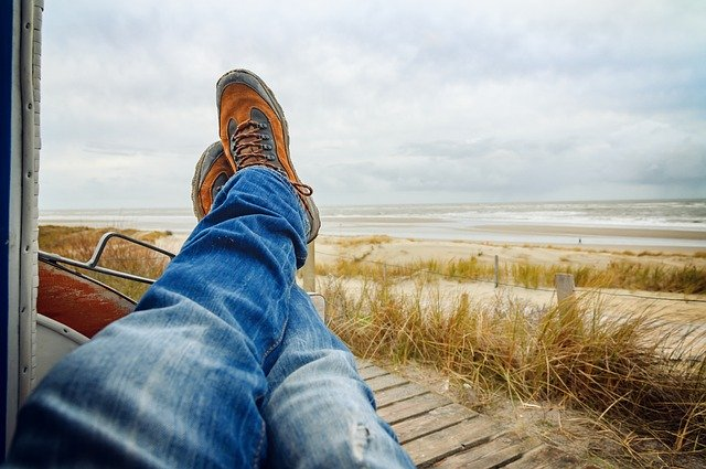 man kicking back and propping his feet on the window to the view of a beach