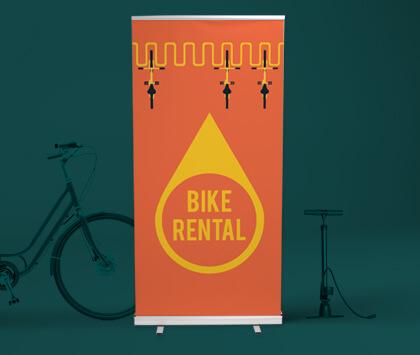 A dark green image containing a printed orange bike rental roller banner.