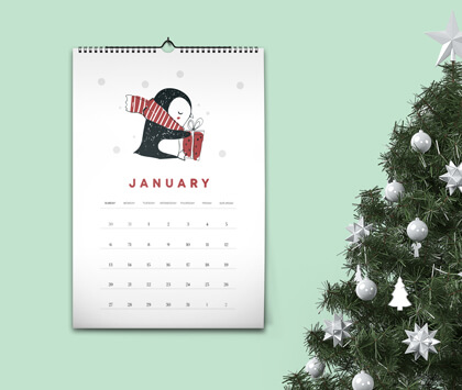 A wall calendar showing a penguin and the month of January on a light green wall.