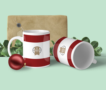 Two red and white striped mugs on a light green background with christmas decorations around them