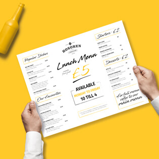Two hands holding a lunch menu with price lists on with a yellow background.