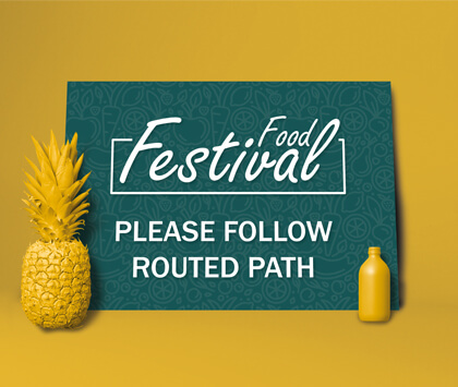 A dark green food festival sign with clear directions on a yellow background.