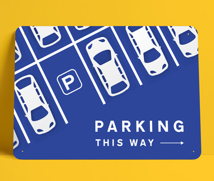 A blue directional parking sign on a yellow background.